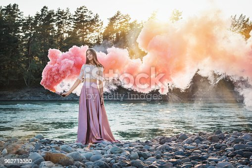 girl with a smoke bomb on the bank of a mountain river with pink and red smoke and forest against a background