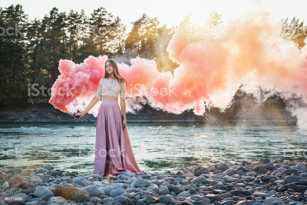chica con un smoke bomb en la orilla de un río de montaña con rosa y rojo humo y bosque en un fondo - foto de stock