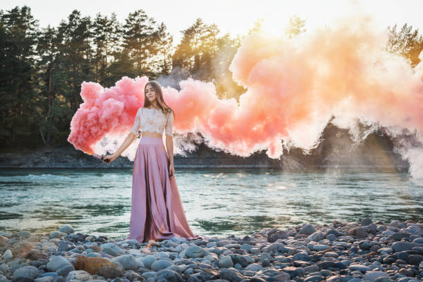 mädchen mit einer smoke bomb am ufer des gebirgsflusses mit rosa und roten rauch und wald auf einem hintergrund - damen rock pink stock-fotos und bilder