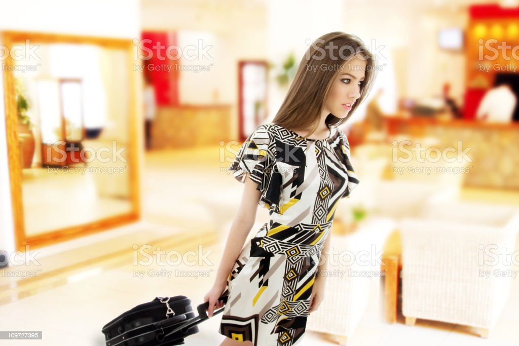 Girl with a suitcase at the hotel reception royalty-free stock photo