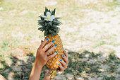 ターコイズ ブルーのマニキュアで女の子が彼女の手で熟したパイナップルを保持します。
