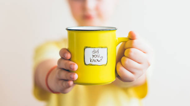 A girl with a yellow cup in her hand, on which was written Did you know A girl in a yellow T-shirt with a yellow cup in her hand, on which was written Did you know. Interesting fact. diad stock pictures, royalty-free photos & images