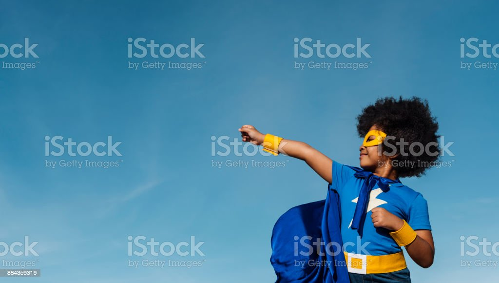 Girl with afro playing superhero stock photo