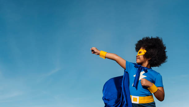 girl with afro playing superhero - forza foto e immagini stock