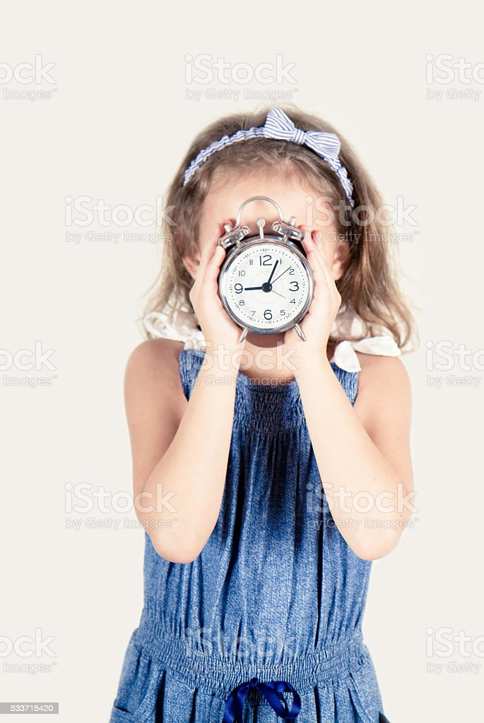 girl with alarm clock in hand stock photo