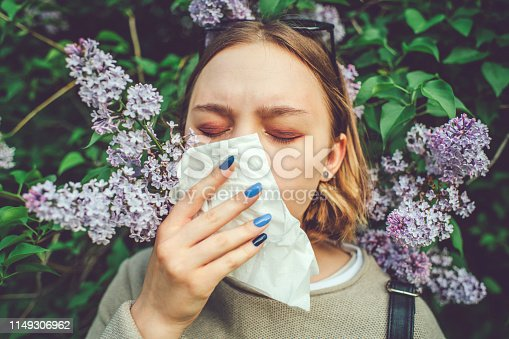 Allergic teenage girl cleaning nose in park