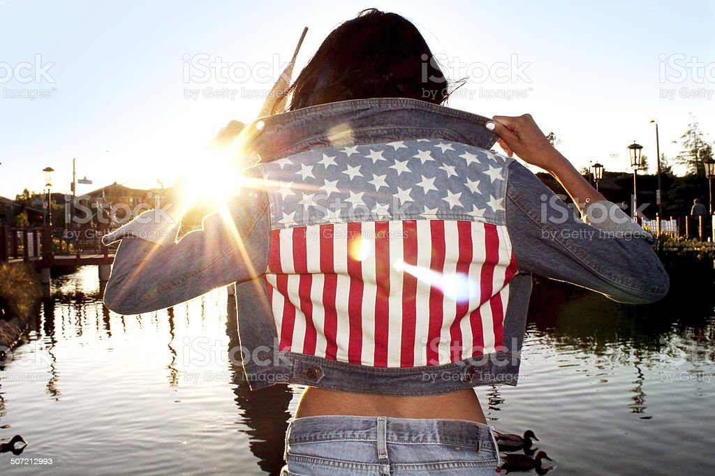 Girl With American Flag Jacket With Sunset stock photo