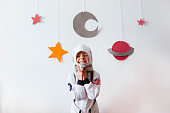 little girl with an astronaut costume at home