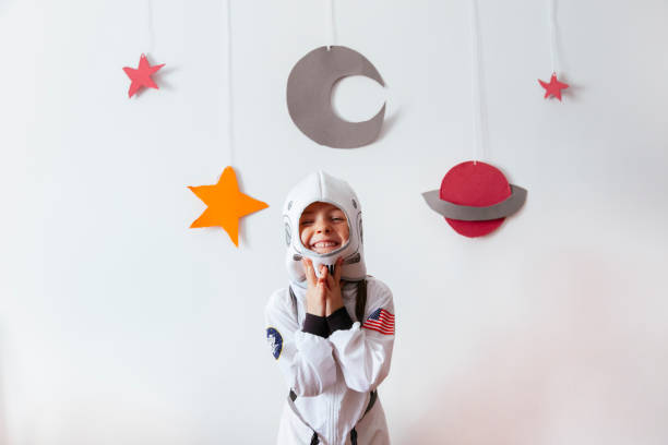 girl with an astronaut costume at home little girl with an astronaut costume at home dressing up stock pictures, royalty-free photos & images