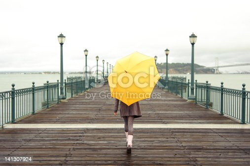 Pretty African American girl walking with umbrella on the pier in San Francisco
