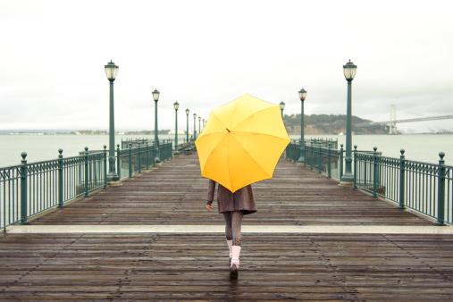A girl with an umbrella on a San Francisco pier