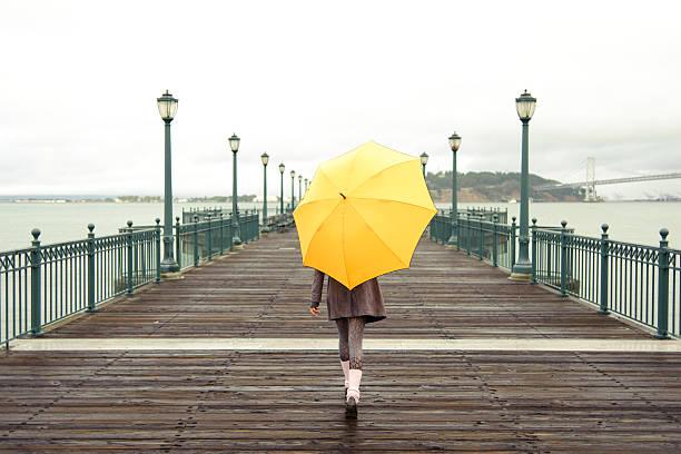 A girl with an umbrella on a San Francisco pier stock photo