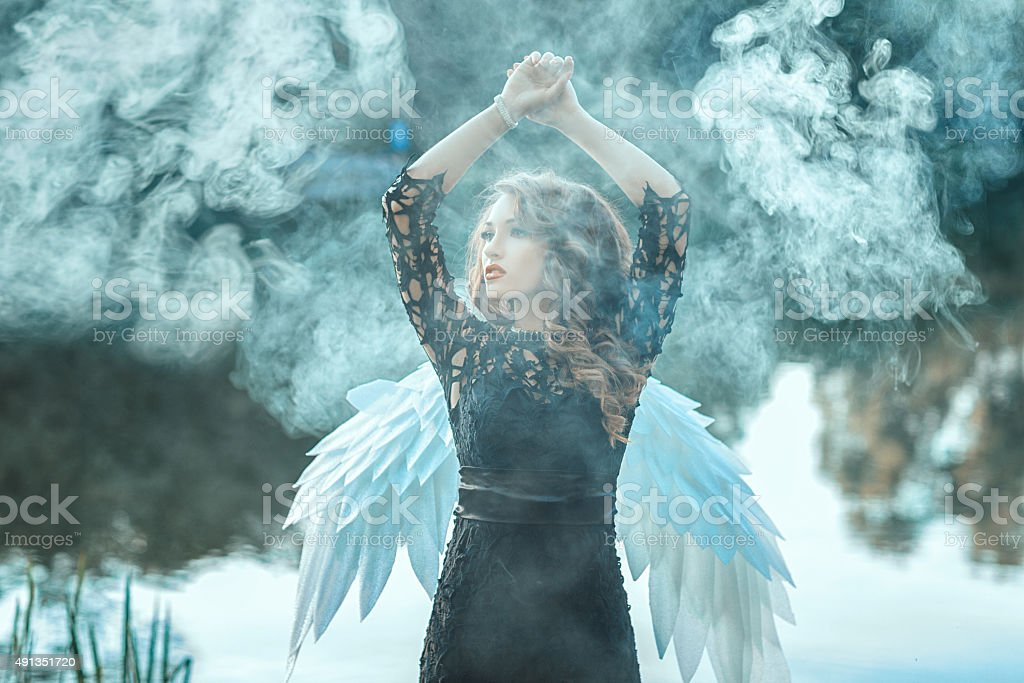 Girl with angel wings is shrouded in smoke. stock photo