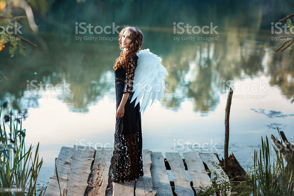 Girl with angel wings standing on the pier and smiling. stock photo
