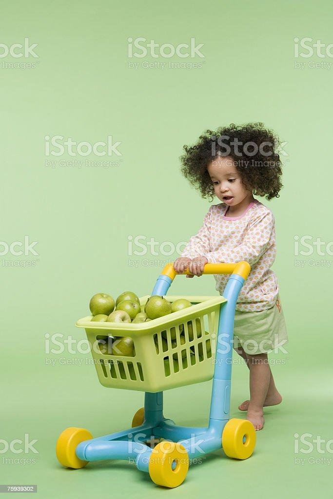 Ragazza con mele nel carrello della spesa - foto stock