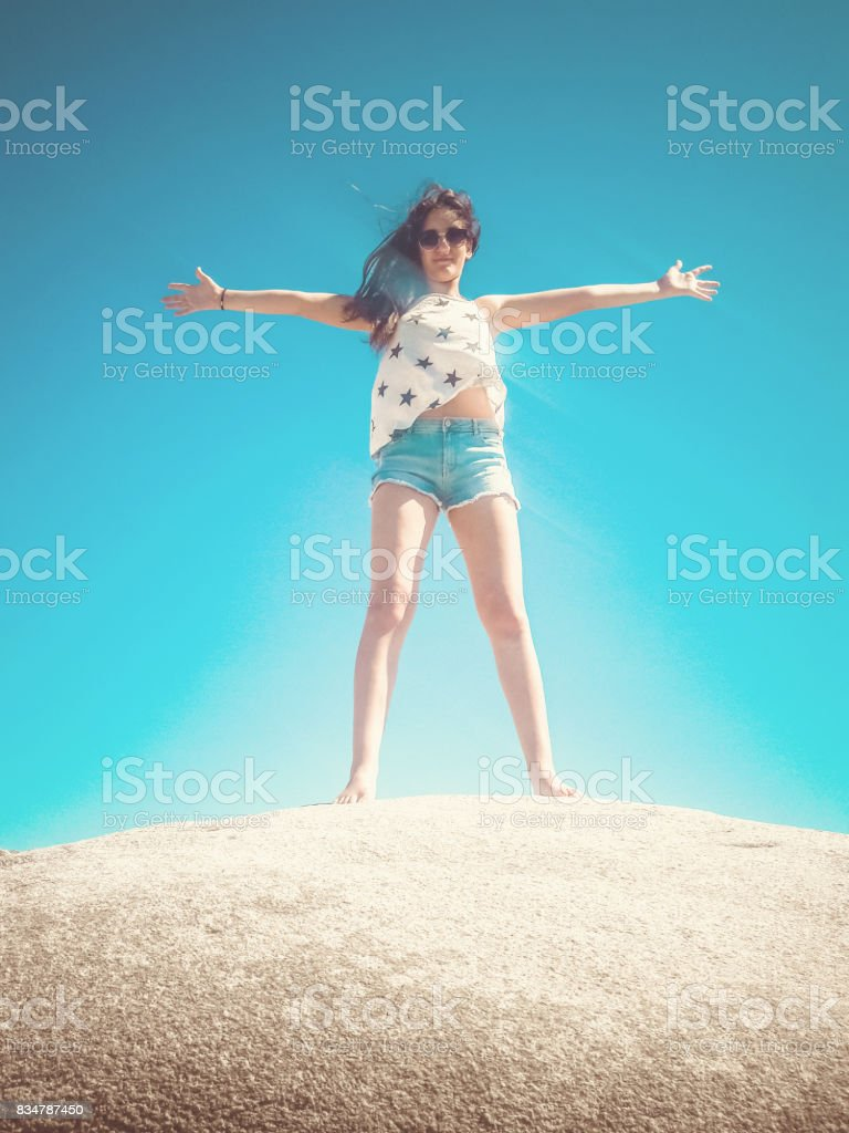 Girl with arms outstretched standing on a big stone stock photo