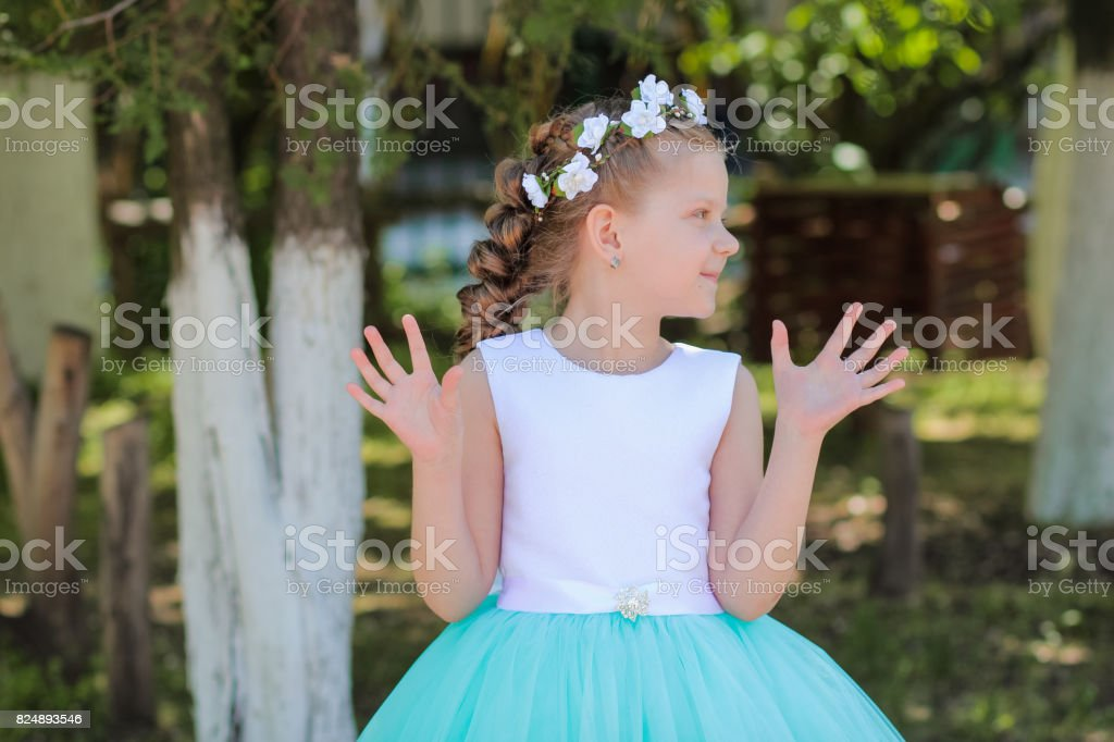 girl with arms raised looks aside, child with a wreath of artificial flowers on her head stock photo