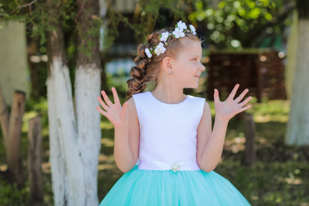 girl with arms raised looks aside, child with a wreath of artificial flowers on her head - diadem stock pictures, royalty-free photos & images