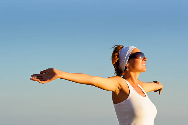 girl with arms raised towards the sky stock photo