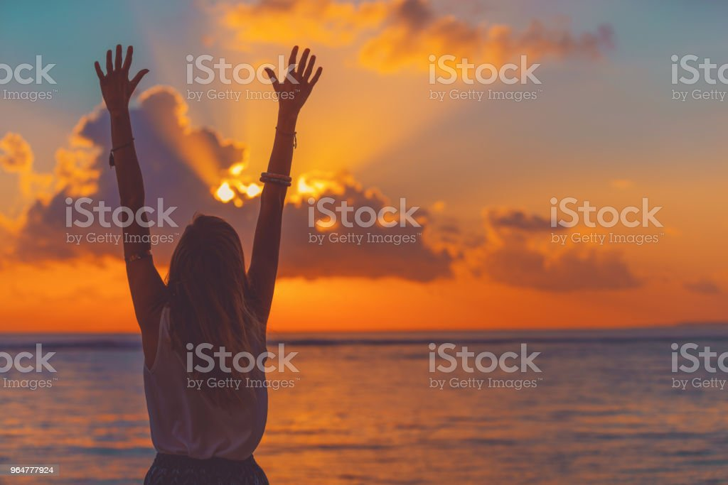 Girl with arms wide open enjoying sea / ocean scenery in sunset. royalty-free stock photo