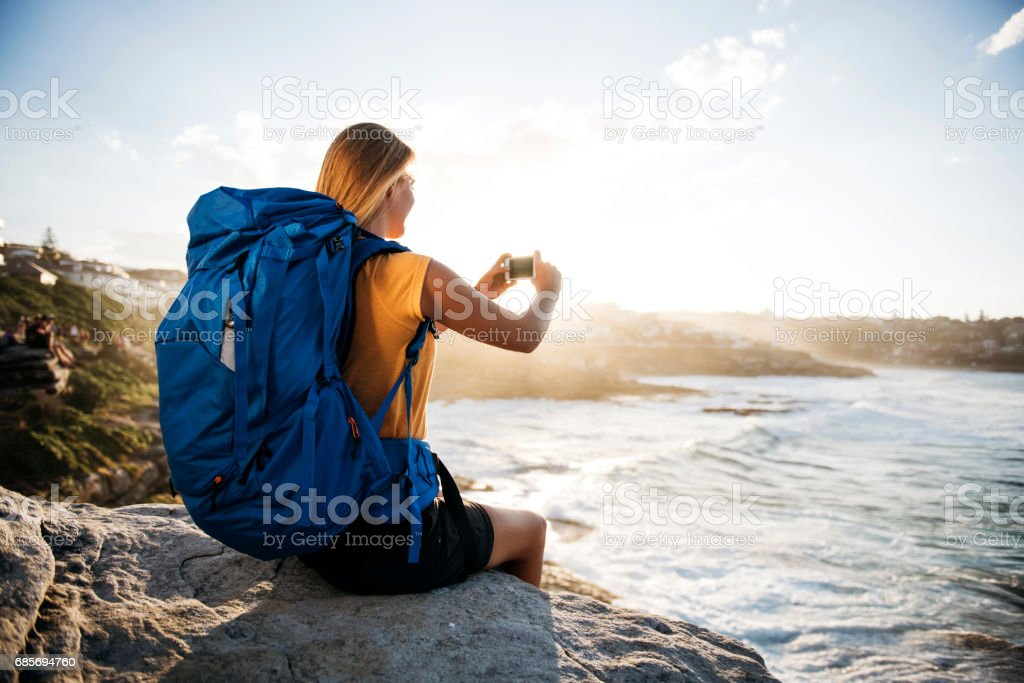 Girl with backpack making a photo royalty-free stock photo