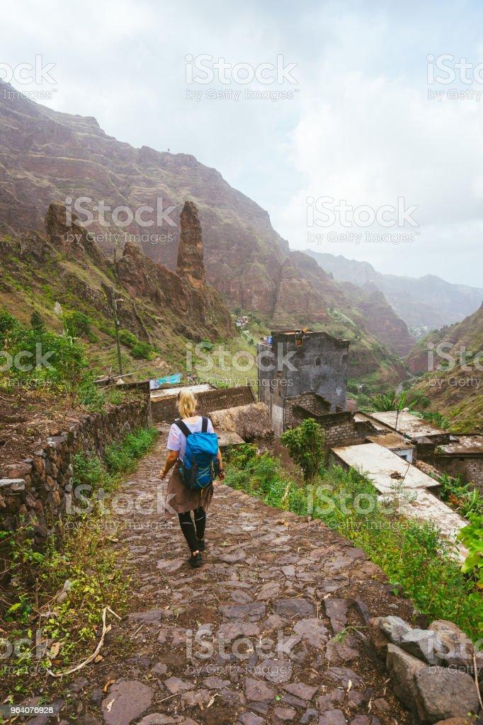 緑豊かな Xo Xo 渓谷をトレッキング ルートに沿って歩いてバックパックを持つ少女。山の峰と地元の村が表示されます前に。サント Antao 島カーボベルデ - ハイキングのロイヤリティフリーストックフォト