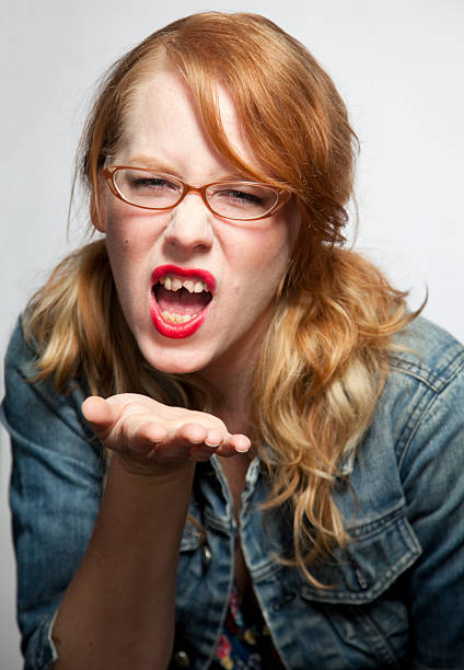 girl with bad teeth blows a kiss - ugly girl stock photos and pictures