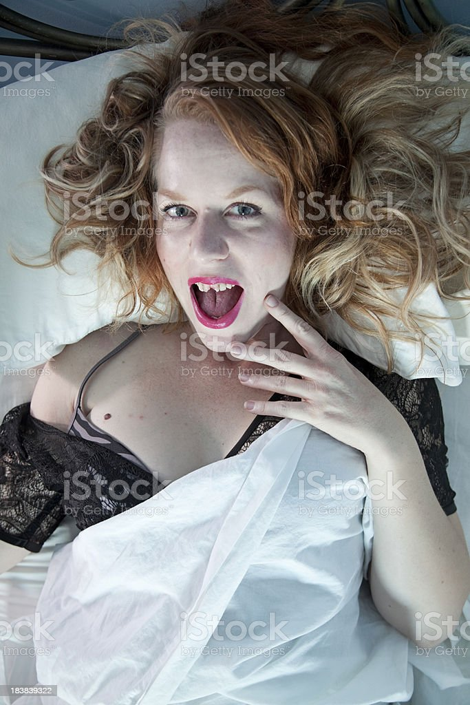 Girl with bad teeth in bed. stock photo
