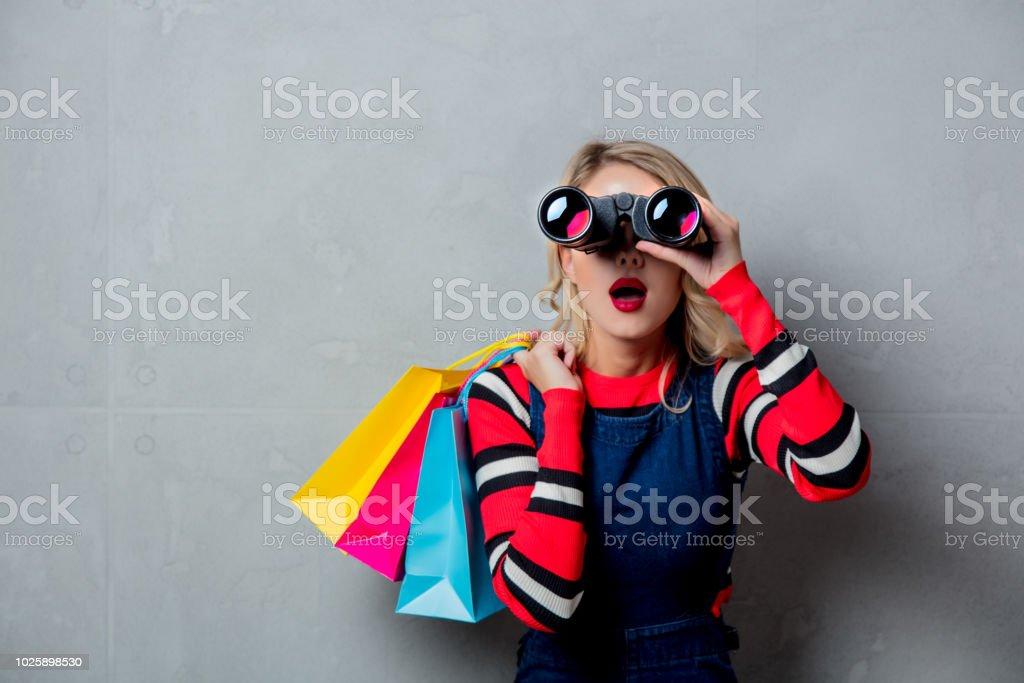 girl with bags and binoculars stock photo