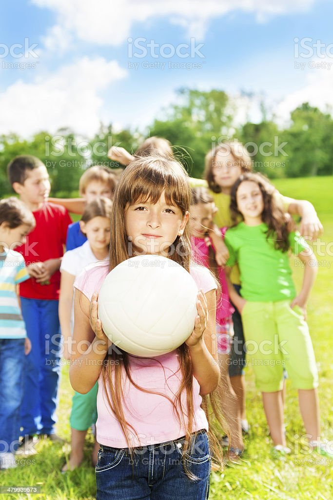 Girl with ball and her team stock photo