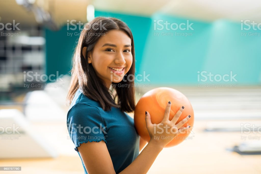 Smiling teenage girl with ball having fun at bowling alley in club