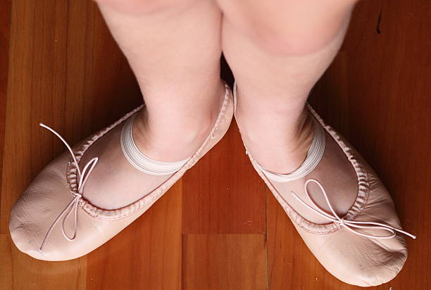 Girl with ballet shoes standing in first position stock photo