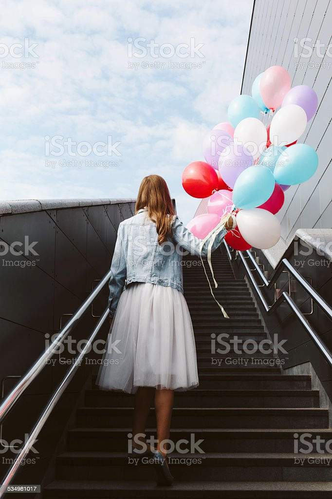girl with balloons in her hand stock photo