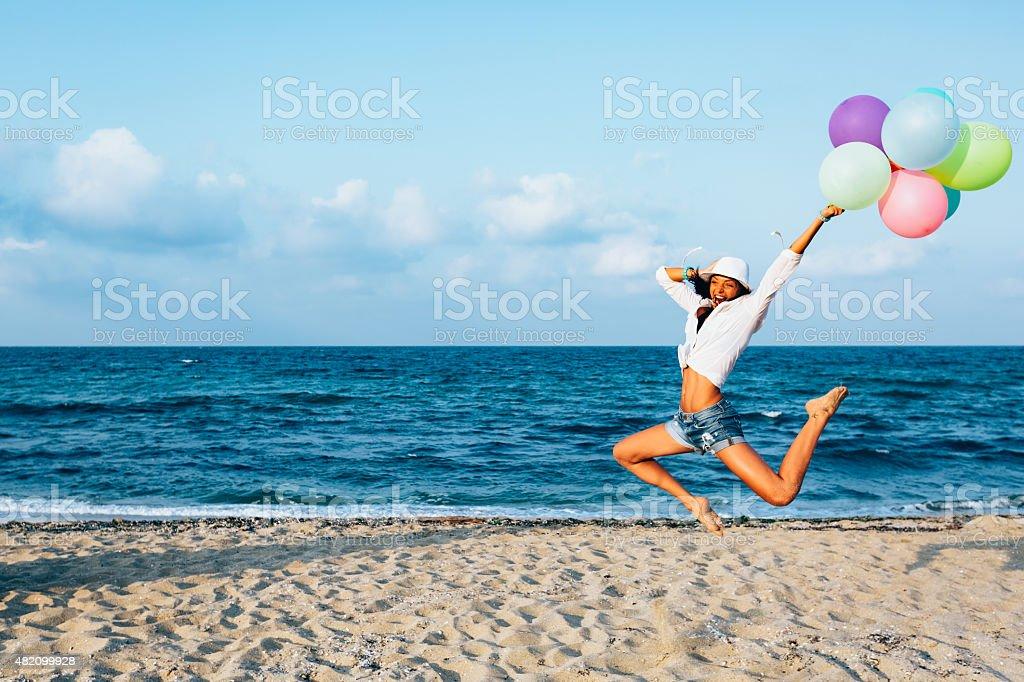 Fille avec des ballons de sauter de joie sur la plage - Photo