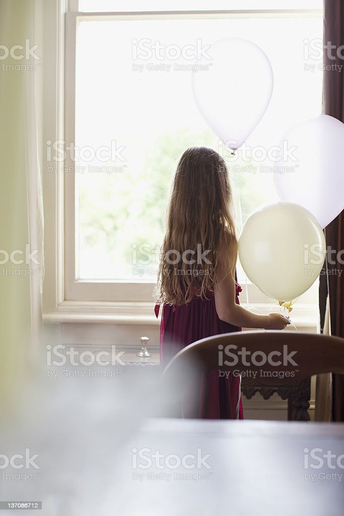 Girl with balloons looking out window royalty-free stock photo