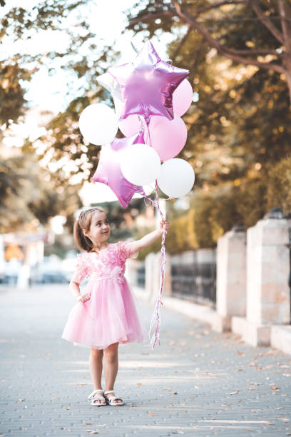 Girl with balloons outdoors stock photo