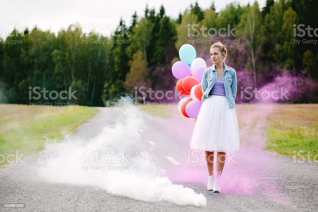 girl with balloons walking down the road stock photo