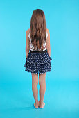 Girl with beautiful natural brown hair isolated on blue
