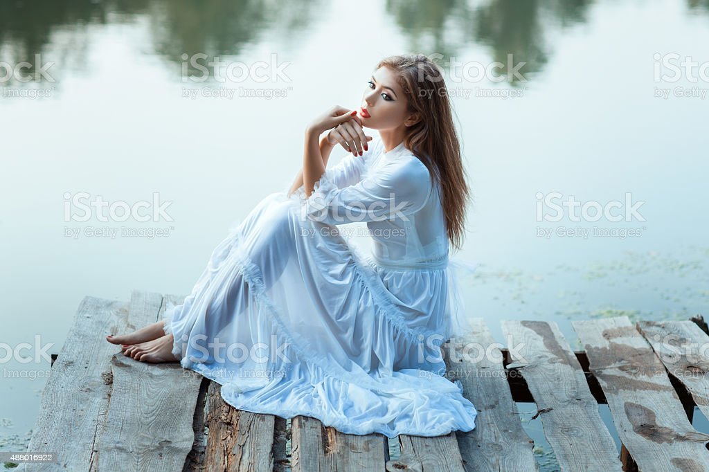 Girl with big eyes sitting on the wharf bored. stock photo