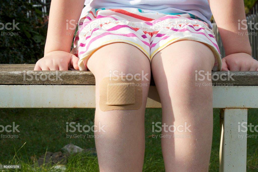 Girl with big plaster on her knee - foto de stock