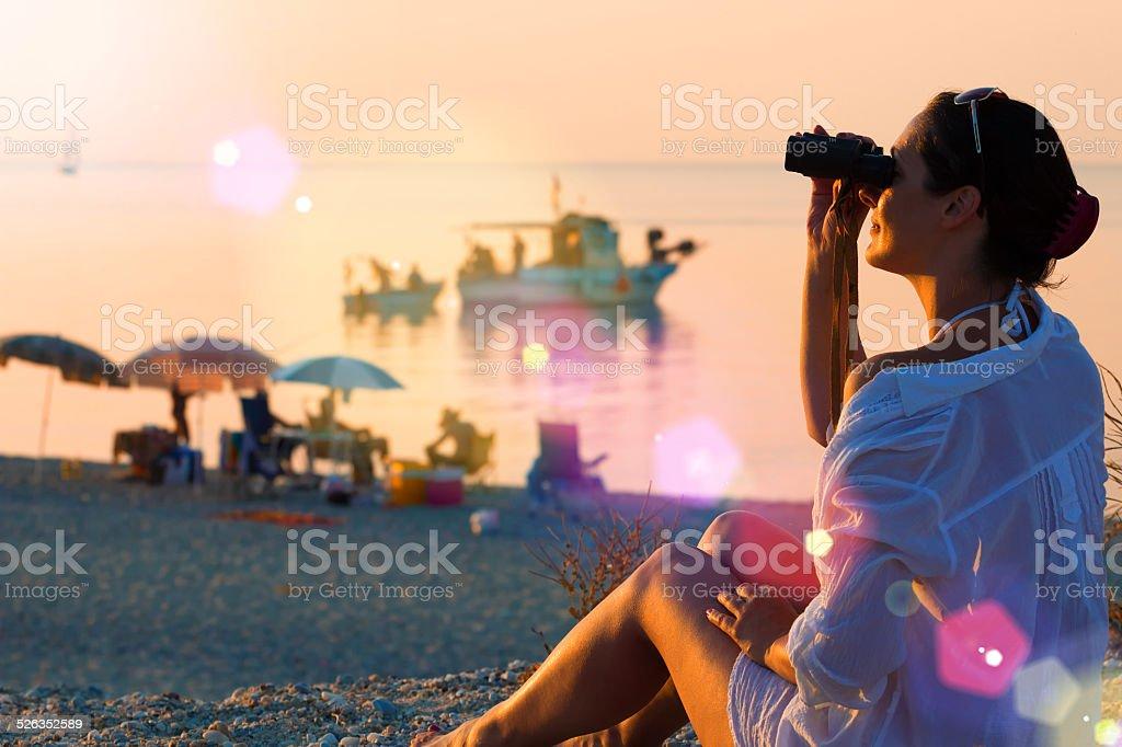 Girl with binoculars on the coast stock photo