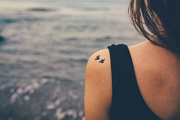 girl with birds tattooed on shoulder. freedom concept - tattoo stock photos and pictures