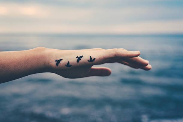 Mädchen mit Vögeln tattooed auf der hand. Freiheit-Konzept – Foto