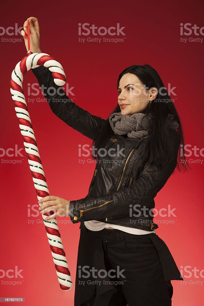Girl with black hair wearing leather jacket holding Christmas candycane stock photo