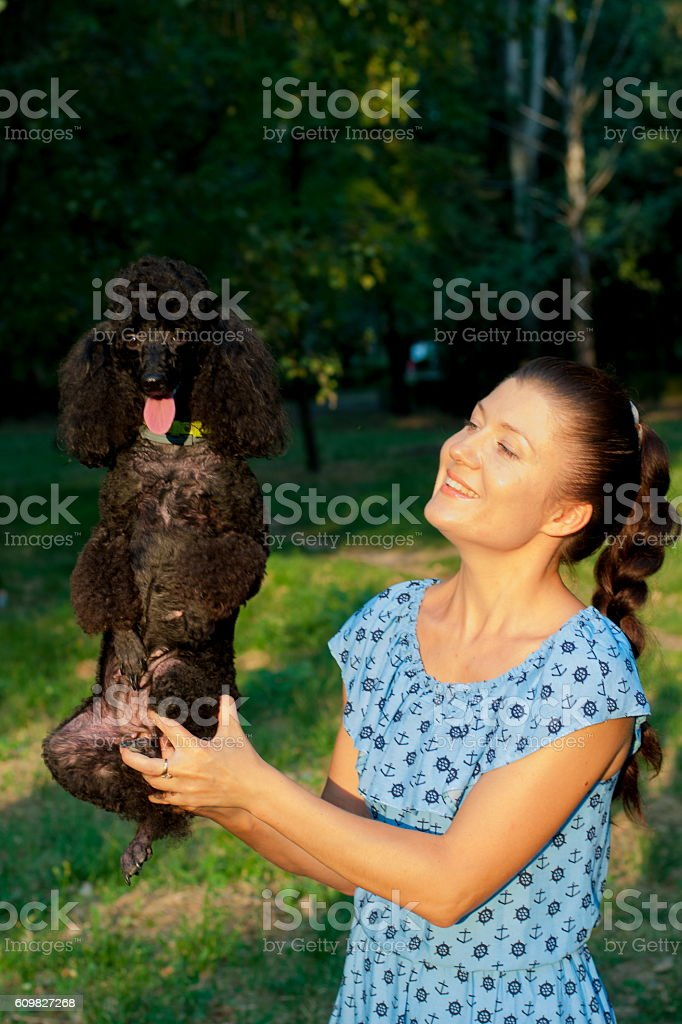 girl with black poodle stock photo