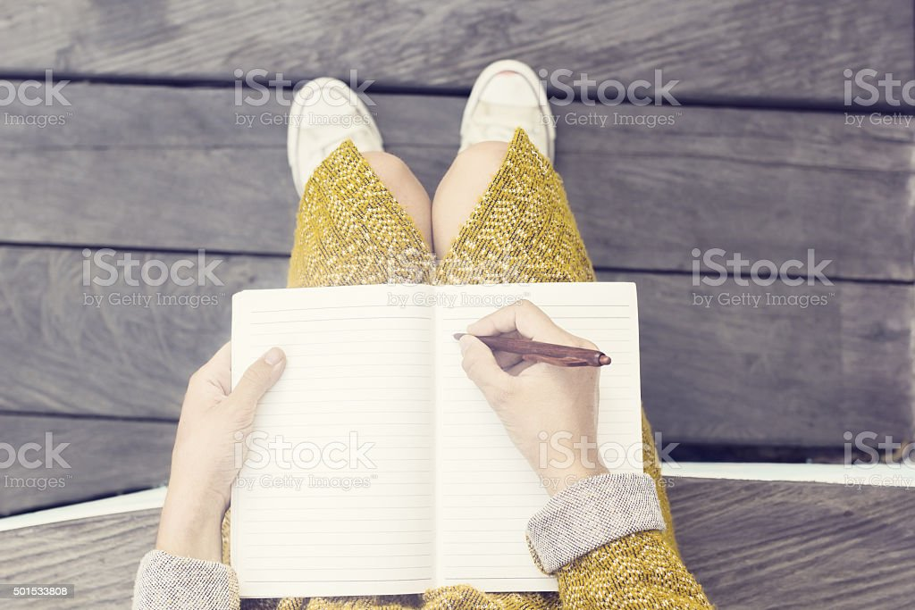 Girl with blank diary and pen sitting on wooden bench stock photo