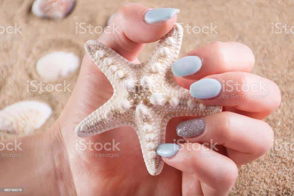 Girl With Blue Manicure Nails Polish Holding Starfish In Hand Stock Photo Download Image Now Istock