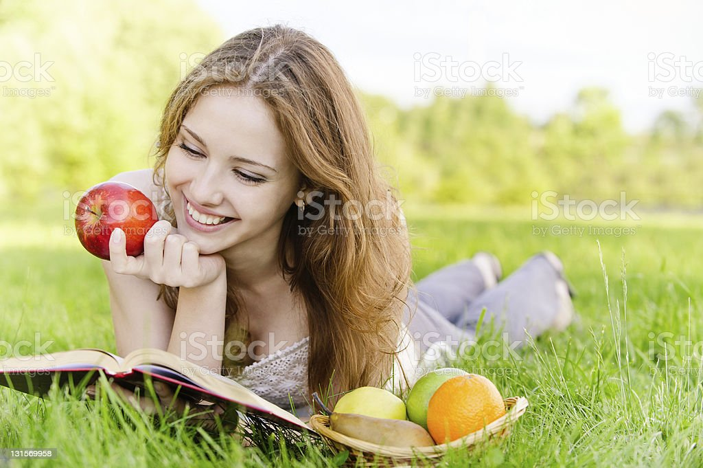 Girl with book and apples royalty-free stock photo