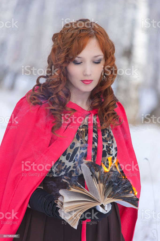 Girl with book burning stock photo