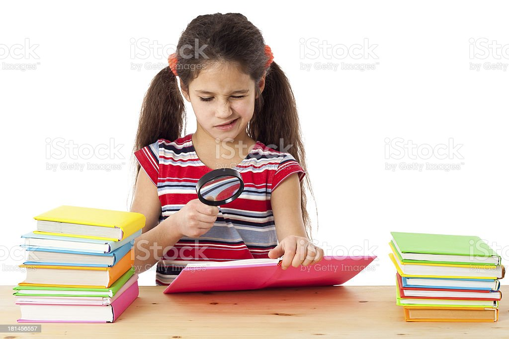 Girl with books and magnifier stock photo